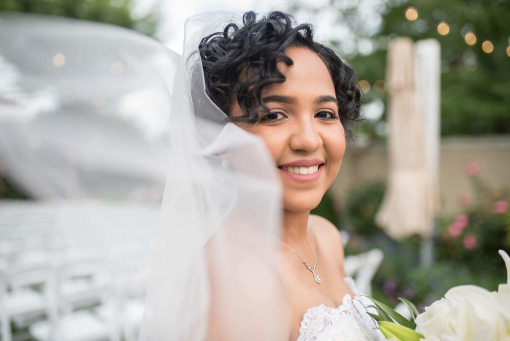 Bride smiling at camera with veil drifting in wind.
